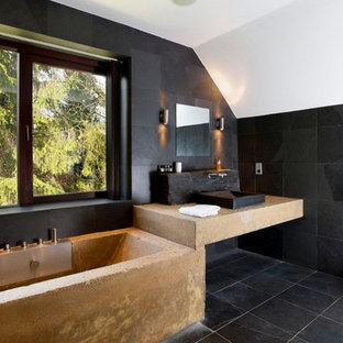 Photo of a contemporary ensuite bathroom in Kent with a built-in bath, black tiles, a vessel sink, black floors and beige worktops.
