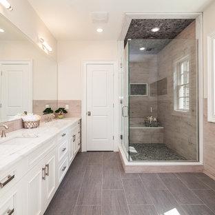 Modelo de cuarto de baño principal, clásico renovado, con puertas de armario blancas, suelo de baldosas de porcelana, encimera de cuarzo compacto, armarios con paneles empotrados, bañera exenta, ducha esquinera, baldosas y/o azulejos beige, baldosas y/o azulejos negros, baldosas y/o azulejos grises, suelo de baldosas tipo guijarro, paredes beige, lavabo bajoencimera y ducha con puerta con bisagras