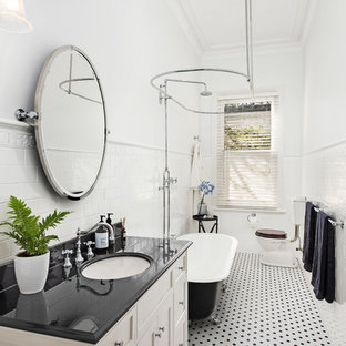 This is an example of a traditional bathroom in Melbourne with recessed-panel cabinets, white cabinets, a claw-foot tub, a shower/bathtub combo, a two-piece toilet, black and white tile, white tile, subway tile, white walls, an undermount sink, a shower curtain and black benchtops.