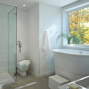 Idée de décoration pour une grand salle de bain principale design avec une baignoire indépendante, béton au sol, un WC séparé, un carrelage blanc, un lavabo intégré, une cabine de douche à porte battante, des portes de placard blanches, une douche d'angle, un carrelage métro, un mur blanc et un sol gris.