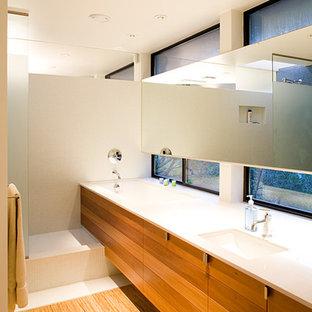 Diseño de cuarto de baño principal, moderno, de tamaño medio, con armarios con paneles lisos, puertas de armario de madera oscura, baldosas y/o azulejos de cerámica, paredes blancas, encimera de cuarcita, bañera encastrada sin remate, ducha esquinera, baldosas y/o azulejos blancos, suelo de contrachapado y lavabo bajoencimera