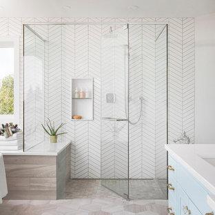 Klassisk inredning av ett stort vit vitt en-suite badrum, med luckor med infälld panel, blå skåp, vita väggar, ett undermonterad handfat, grått golv, ett fristående badkar, en dusch i en alkov, porslinskakel, bänkskiva i kvarts och dusch med gångjärnsdörr