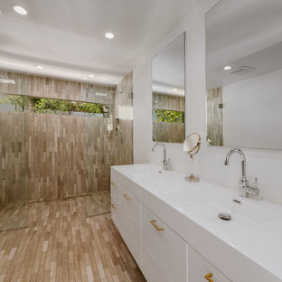 Large tuscan 3/4 bathroom photo in Los Angeles with white walls, flat-panel cabinets, a one-piece toilet and an integrated sink