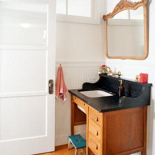Immagine di una stanza da bagno con doccia country di medie dimensioni con lavabo sottopiano, consolle stile comò, ante in legno scuro, top in saponaria, pareti bianche e pavimento in legno massello medio