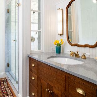 Modelo de cuarto de baño principal, de estilo de casa de campo, de tamaño medio, con lavabo bajoencimera, armarios estilo shaker, puertas de armario de madera en tonos medios, encimera de mármol, ducha empotrada, baldosas y/o azulejos blancos, paredes blancas, suelo de madera en tonos medios y encimeras grises