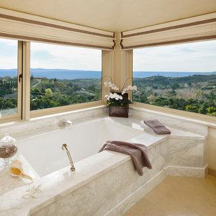 Idee per una stanza da bagno padronale tradizionale con top in marmo, vasca sottopiano, piastrelle beige, piastrelle in pietra, pareti beige e pavimento in laminato