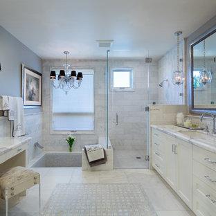 Modelo de cuarto de baño principal, clásico renovado, de tamaño medio, con lavabo bajoencimera, armarios estilo shaker, puertas de armario blancas, encimera de mármol, ducha a ras de suelo, baldosas y/o azulejos grises, baldosas y/o azulejos en mosaico, paredes grises, suelo de mármol, jacuzzi, suelo blanco y ducha con puerta con bisagras