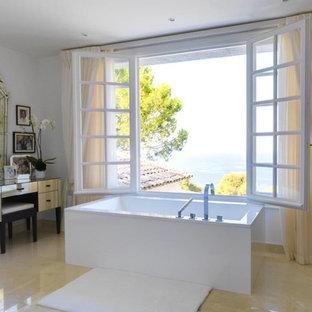 Réalisation d'une grand salle de bain principale tradition avec un mur blanc et une baignoire indépendante.