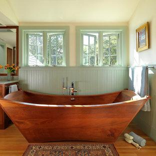 Ejemplo de cuarto de baño principal, de estilo americano, con armarios con paneles empotrados, puertas de armario de madera oscura, bañera exenta, paredes beige, suelo de madera en tonos medios y suelo marrón