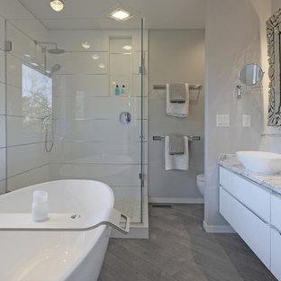 Réalisation d'une salle de bain principale design de taille moyenne avec un placard à porte plane, des portes de placard blanches, une baignoire indépendante, une douche d'angle, un WC à poser, un carrelage blanc, des carreaux de porcelaine, un mur gris, un sol en bois brun, une vasque, un plan de toilette en marbre, un sol gris et une cabine de douche à porte battante.