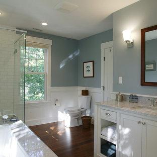 Inredning av ett klassiskt mellanstort en-suite badrum, med vita skåp, ett undermonterat badkar, en toalettstol med separat cisternkåpa, vit kakel, keramikplattor, blå väggar, mörkt trägolv, ett undermonterad handfat, marmorbänkskiva, luckor med profilerade fronter och en hörndusch