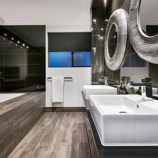 Contemporary master bathroom in Perth with flat-panel cabinets, black cabinets, a drop-in tub, black tile, black walls, a vessel sink, brown floor and black benchtops.