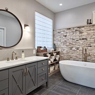Bild på ett mellanstort vintage en-suite badrum, med möbel-liknande, grå skåp, ett fristående badkar, en hörndusch, grå kakel, travertinkakel, vita väggar, klinkergolv i keramik, ett undermonterad handfat, bänkskiva i kvarts och grått golv