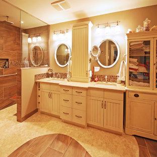 エドモントンの大きいトランジショナルスタイルのおしゃれなマスターバスルーム (インセット扉のキャビネット、ヴィンテージ仕上げキャビネット、アルコーブ型浴槽、段差なし、一体型トイレ、茶色いタイル、磁器タイル、茶色い壁、磁器タイルの床、アンダーカウンター洗面器、珪岩の洗面台) の写真
