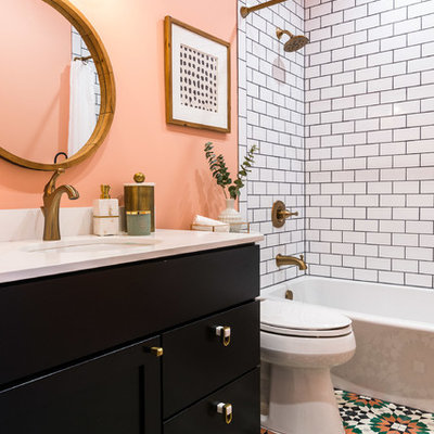 Mid-sized trendy 3/4 white tile and subway tile multicolored floor and ceramic tile bathroom photo in DC Metro with recessed-panel cabinets, black cabinets, pink walls, an undermount sink, white countertops, a two-piece toilet and solid surface countertops