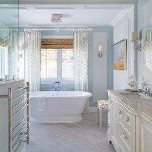 ボストンの中サイズのビーチスタイルのおしゃれなマスターバスルーム (家具調キャビネット、白いキャビネット、置き型浴槽、コーナー設置型シャワー、一体型トイレ、セラミックタイル、青い壁、セラミックタイルの床、アンダーカウンター洗面器、珪岩の洗面台、ベージュの床、開き戸のシャワー、マルチカラーの洗面カウンター) の写真