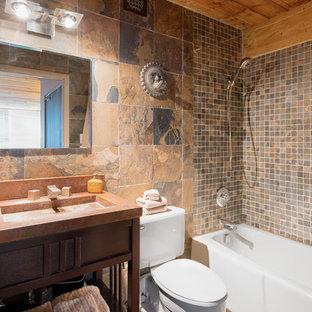 Foto de cuarto de baño con ducha, rural, de tamaño medio, con armarios abiertos, puertas de armario de madera en tonos medios, bañera empotrada, combinación de ducha y bañera, sanitario de una pieza, baldosas y/o azulejos marrones, baldosas y/o azulejos grises, baldosas y/o azulejos de pizarra, paredes beige, suelo de pizarra, lavabo integrado, encimera de ónix, suelo marrón y ducha con cortina