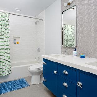 Imagen de cuarto de baño infantil, actual, con armarios con paneles lisos, puertas de armario azules, bañera empotrada, combinación de ducha y bañera, baldosas y/o azulejos grises, baldosas y/o azulejos blancos, paredes blancas, suelo de cemento, lavabo bajoencimera y ducha con cortina