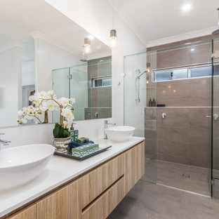 Inspiration for a large beach style 3/4 bathroom in Brisbane with flat-panel cabinets, light wood cabinets, an alcove shower, gray tile, white walls, a vessel sink, grey floor, a hinged shower door, white benchtops, a double vanity and a floating vanity.
