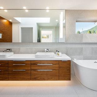 Großes Modernes Badezimmer mit hellbraunen Holzschränken, grauen Fliesen, Quarzwerkstein-Waschtisch, weißem Boden, weißer Waschtischplatte, flächenbündigen Schrankfronten, Doppelwaschbecken und schwebendem Waschtisch in Vancouver