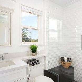 Small trendy master white tile and subway tile porcelain tile and white floor bathroom photo in San Diego with shaker cabinets, white cabinets, a one-piece toilet, white walls, an undermount sink, quartz countertops, a hinged shower door and white countertops