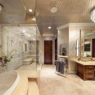 Идея дизайна: огромная главная ванная комната в морском стиле с фасадами с выступающей филенкой, фасадами цвета дерева среднего тона, накладной ванной, двойным душем, бежевой плиткой, плиткой из травертина, серыми стенами, полом из травертина, столешницей из известняка, бежевым полом и душем с распашными дверями