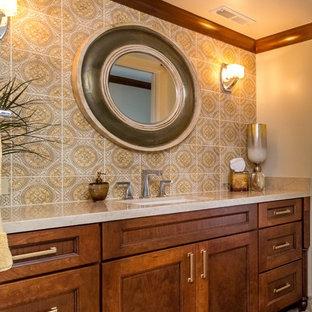 Immagine di una grande stanza da bagno con doccia tradizionale con lavabo sottopiano, ante con riquadro incassato, ante in legno scuro, top in marmo, piastrelle beige, piastrelle in ceramica, pareti gialle e pavimento in travertino