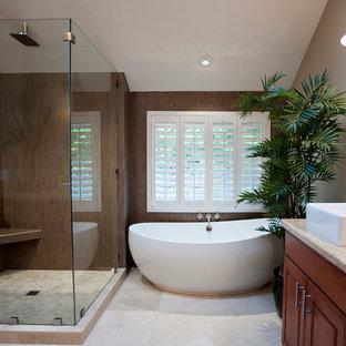 Пример оригинального дизайна: большая главная ванная комната в современном стиле с отдельно стоящей ванной, настольной раковиной, фасадами с декоративным кантом, фасадами цвета дерева среднего тона, угловым душем, бежевыми стенами, полом из керамической плитки, столешницей из известняка и душем с распашными дверями