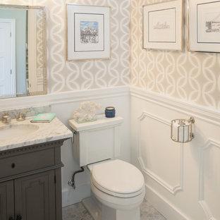 Klassisches Badezimmer mit verzierten Schränken, grauen Schränken, Wandtoilette mit Spülkasten, beiger Wandfarbe und Unterbauwaschbecken in San Diego