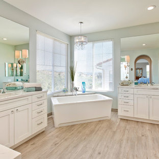 Large beach style master porcelain tile porcelain tile and beige floor freestanding bathtub photo in San Diego with shaker cabinets, white cabinets, a two-piece toilet, blue walls, an undermount sink and quartz countertops