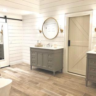 Großes Country Badezimmer En Suite mit Schrankfronten mit vertiefter Füllung, grauen Schränken, weißer Wandfarbe, hellem Holzboden, Unterbauwaschbecken, Granit-Waschbecken/Waschtisch, braunem Boden und weißer Waschtischplatte in Bridgeport