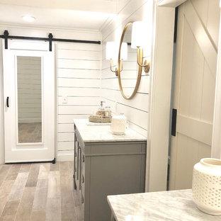 Lantlig inredning av ett stort vit vitt en-suite badrum, med luckor med infälld panel, grå skåp, vita väggar, ljust trägolv, ett undermonterad handfat, granitbänkskiva och brunt golv