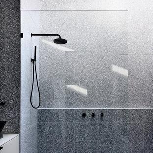 На фото: маленькая главная ванная комната с фасадами с утопленной филенкой, белыми фасадами, открытым душем, инсталляцией, серой плиткой, керамической плиткой, серыми стенами, полом из терраццо, монолитной раковиной, столешницей терраццо, серым полом, открытым душем и белой столешницей с