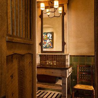 Idee per una grande stanza da bagno padronale rustica con consolle stile comò, ante in legno scuro, piastrelle verdi, pareti beige, lavabo integrato, piastrelle in ceramica, pavimento in mattoni e top marrone