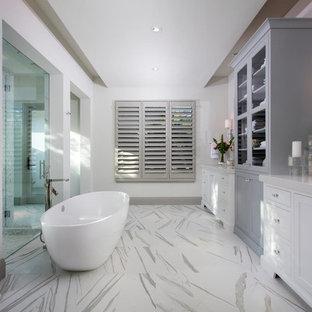 Klassisk inredning av ett en-suite badrum, med luckor med glaspanel, grå skåp, ett fristående badkar, en kantlös dusch, vita väggar, ett undermonterad handfat, flerfärgat golv och dusch med gångjärnsdörr