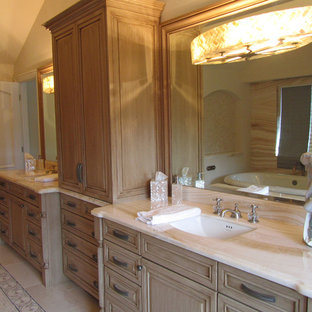 Large traditional master bathroom in Sacramento with raised-panel cabinets, distressed cabinets, a freestanding tub, an alcove shower, a one-piece toilet, beige tile, porcelain tile, beige walls, porcelain floors, an undermount sink and onyx benchtops.