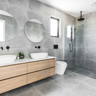 Inspiration for a mid-sized modern master bathroom in Melbourne with flat-panel cabinets, a curbless shower, a one-piece toilet, grey walls, a vessel sink, marble benchtops, grey floor, light wood cabinets, gray tile, cement tile, concrete floors, an open shower and grey benchtops.
