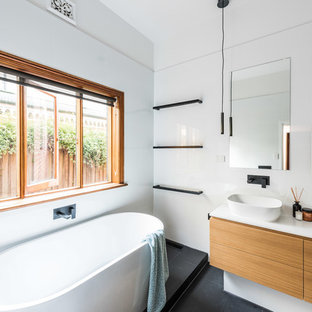 This is an example of a mid-sized modern master bathroom in Melbourne with flat-panel cabinets, a freestanding tub, white tile, ceramic tile, white walls, a vessel sink, engineered quartz benchtops, black floor, medium wood cabinets, a corner shower, a hinged shower door and white benchtops.
