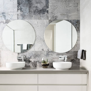 Photo of a contemporary bathroom in Melbourne with flat-panel cabinets, white cabinets, gray tile, a vessel sink, grey floor, grey benchtops and a double vanity.