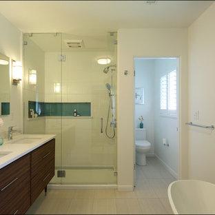 Ejemplo de cuarto de baño principal, vintage, de tamaño medio, con lavabo bajoencimera, armarios tipo mueble, puertas de armario de madera en tonos medios, bañera exenta, ducha empotrada, sanitario de dos piezas, baldosas y/o azulejos azules, baldosas y/o azulejos de vidrio, paredes blancas, suelo de baldosas de cerámica y encimera de cuarzo compacto