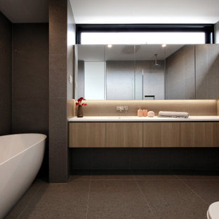 This is an example of a contemporary bathroom in Melbourne with flat-panel cabinets, medium wood cabinets, a freestanding tub, gray tile, grey floor and white benchtops.