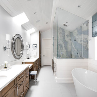 Photo of a contemporary master bathroom in Los Angeles with beaded inset cabinets, medium wood cabinets, a freestanding tub, an alcove shower, white walls, an undermount sink, white floor, a hinged shower door, white benchtops, porcelain floors and solid surface benchtops.