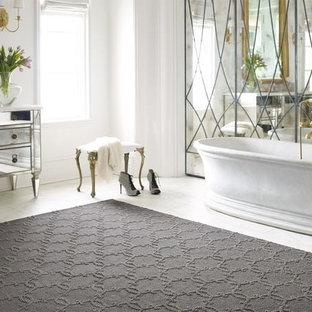 Inredning av ett klassiskt stort en-suite badrum, med ett fristående badkar, vita väggar, släta luckor, skåp i slitet trä, spegel istället för kakel, marmorgolv, marmorbänkskiva och vitt golv