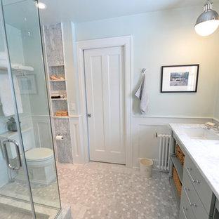Modelo de cuarto de baño con ducha, tradicional, de tamaño medio, con lavabo bajoencimera, armarios tipo mueble, puertas de armario grises, encimera de mármol, ducha esquinera, sanitario de dos piezas, baldosas y/o azulejos grises, paredes grises, suelo de mármol y suelo de baldosas tipo guijarro