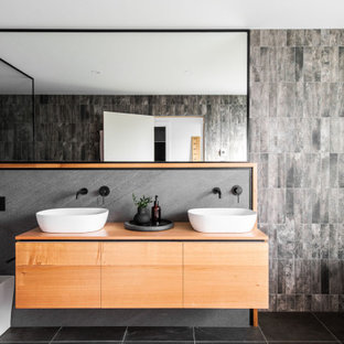 This is an example of a contemporary master bathroom in Hobart with flat-panel cabinets, medium wood cabinets, a freestanding tub, a one-piece toilet, gray tile, grey walls, a vessel sink, wood benchtops, grey floor, brown benchtops, a double vanity and a floating vanity.