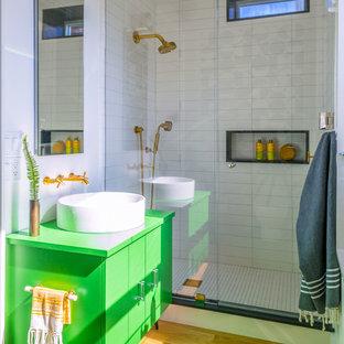 Свежая идея для дизайна: ванная комната в современном стиле с плоскими фасадами, зелеными фасадами, душем в нише, белой плиткой, белыми стенами, паркетным полом среднего тона, душевой кабиной, настольной раковиной, желтым полом и душем с распашными дверями - отличное фото интерьера