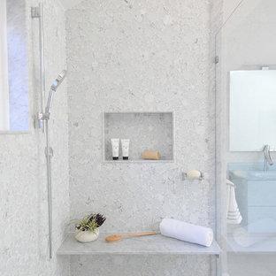 Пример оригинального дизайна: большая главная ванная комната в современном стиле с синими фасадами, отдельно стоящей ванной, унитазом-моноблоком, белой плиткой, стеклянной плиткой, монолитной раковиной, стеклянной столешницей, бежевым полом, душем с распашными дверями, синей столешницей, плоскими фасадами, душем в нише, серыми стенами и полом из керамогранита