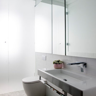 Design ideas for a mid-sized traditional wet room bathroom in Sydney with glass-front cabinets, a wall-mount toilet, white tile, subway tile, white walls, marble floors, a wall-mount sink, white floor, a hinged shower door and white benchtops.