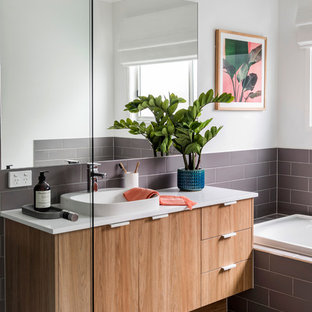 Photo of a beach style 3/4 bathroom in Gold Coast - Tweed with flat-panel cabinets, medium wood cabinets, a drop-in tub, brown tile, white walls, a drop-in sink, beige floor and white benchtops.