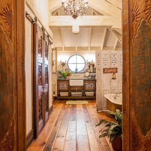 ダラスのシャビーシック調のおしゃれな浴室 (アンダーカウンター洗面器、ヴィンテージ仕上げキャビネット、白い壁、無垢フローリング、ルーバー扉のキャビネット) の写真